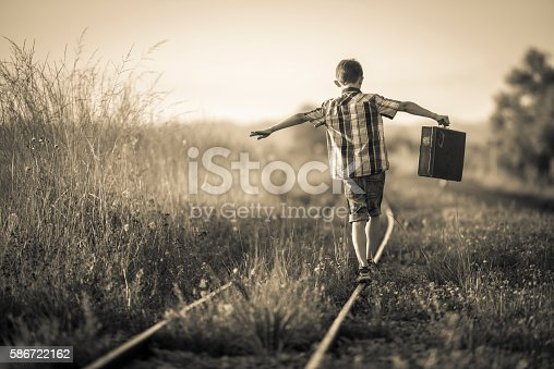 Rear view of a boy holding a suitcase in his outstretched arms. His is balancing jauntily on rails in the evening sun. Selective focus on the boy, photo is sepia toned and vignette added for retro style.
