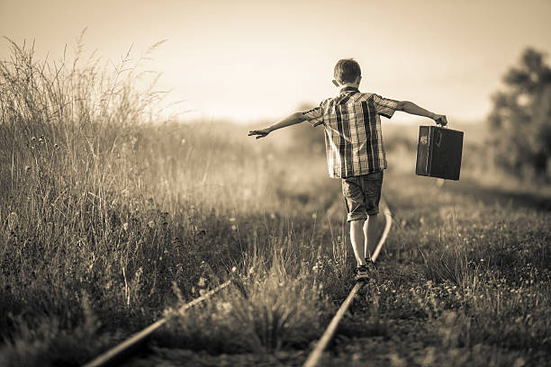 boy with bag balancing on rails - sepia stock photos and pictures
