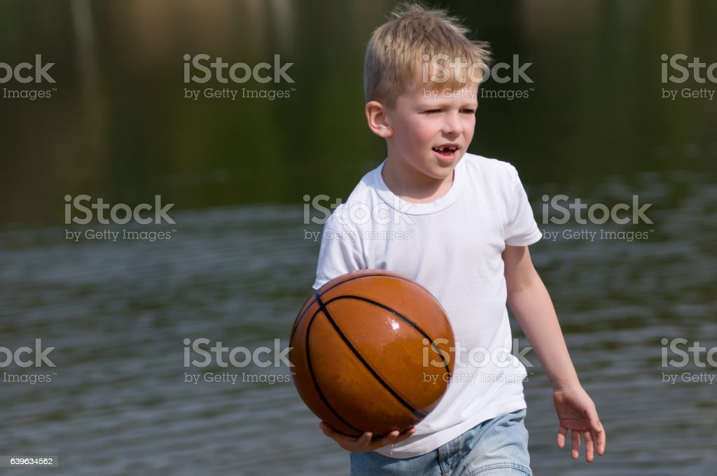 Boy with basketball ball in his hands stock photo