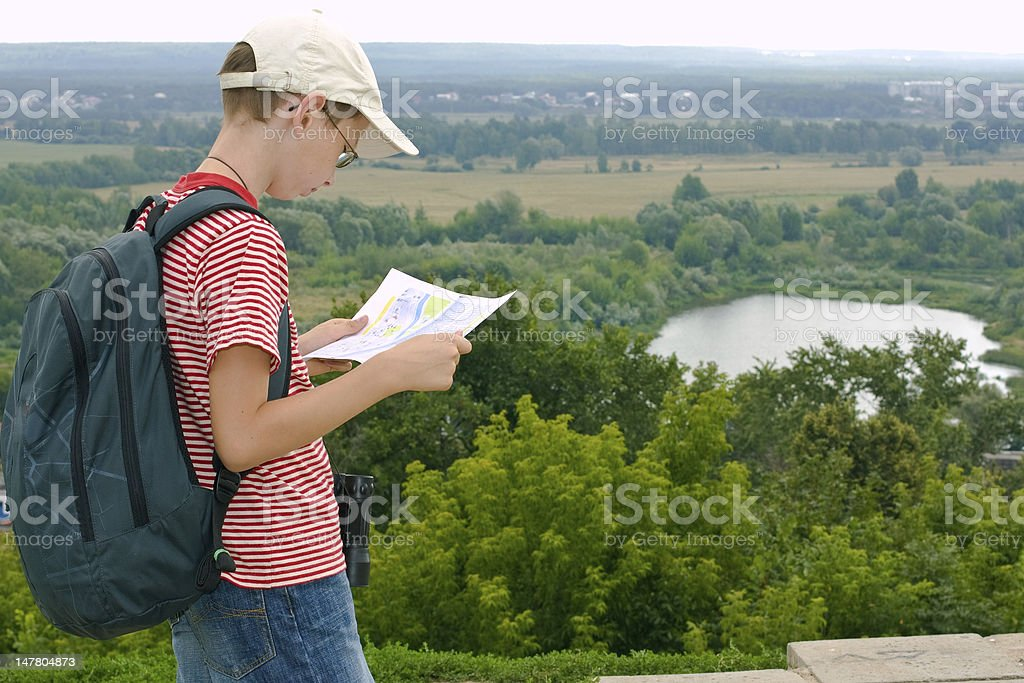 Boy with binoculars, backpack and map stock photo
