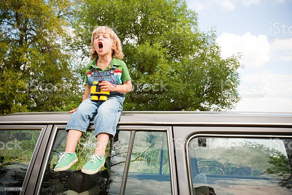 Boy with binoculars, sitting on roof of car stock photo
