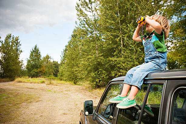 Boy with binoculars, sitting on roof of car  bib overalls boy stock pictures, royalty-free photos & images