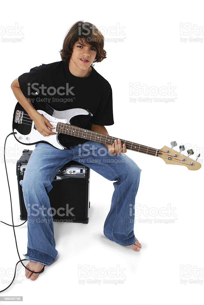 Boy With Black And White Bass Guitar Sitting On Amp stock photo