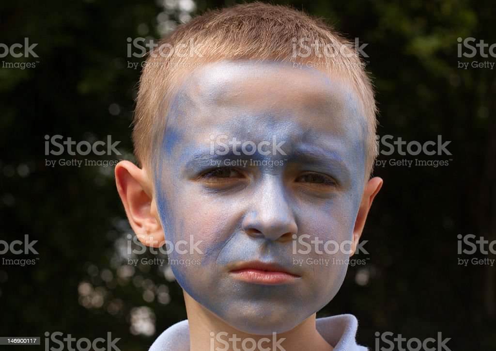 boy with blue painted face stock photo