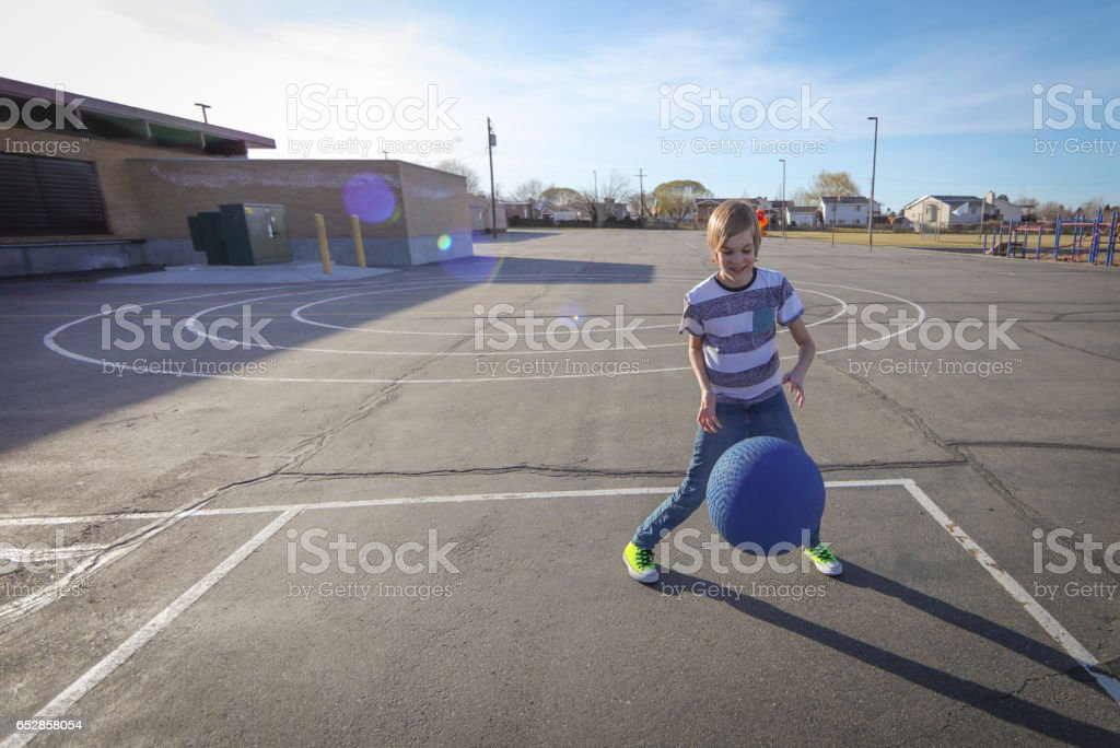 Boy with braces playing with ball stock photo