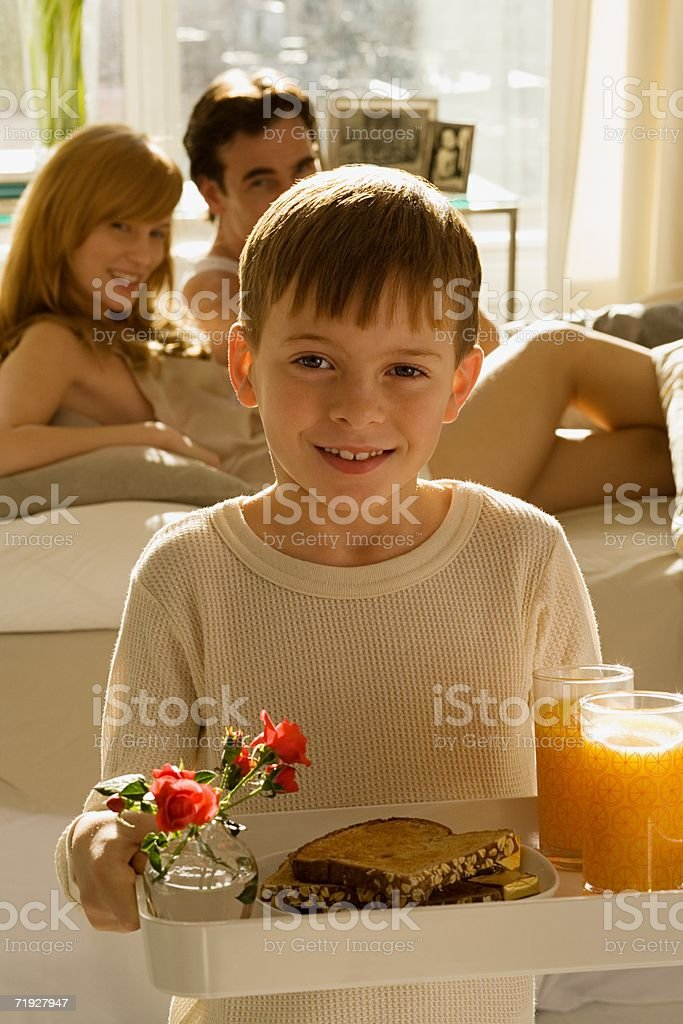 Boy with breakfast for parents royalty-free stock photo