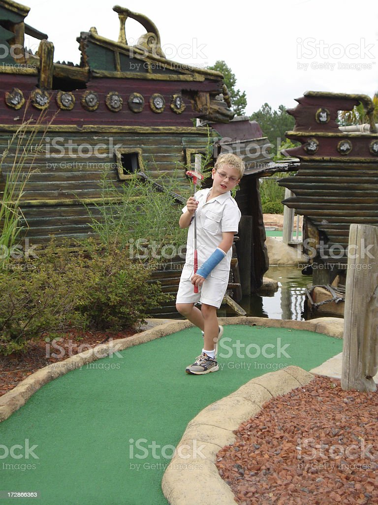 Boy with broken arm plays miniature golf. royalty-free stock photo