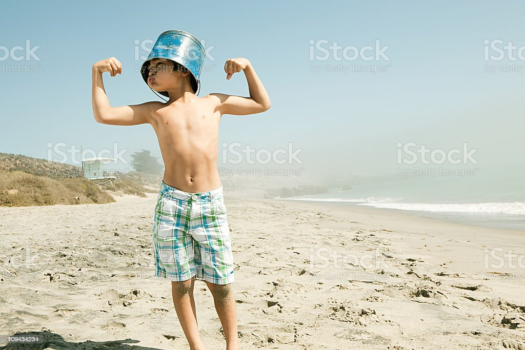 Boy with bucket on head, flexing muscles stock photo