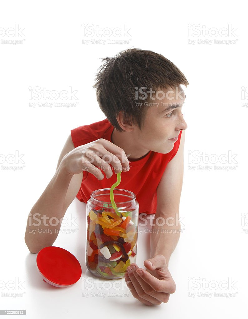 Boy with candy snake looking sideways royalty-free stock photo