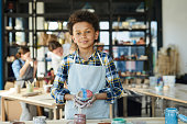 Little schoolboy with painted clay cup standing in front of camera in studio of arts and crafts