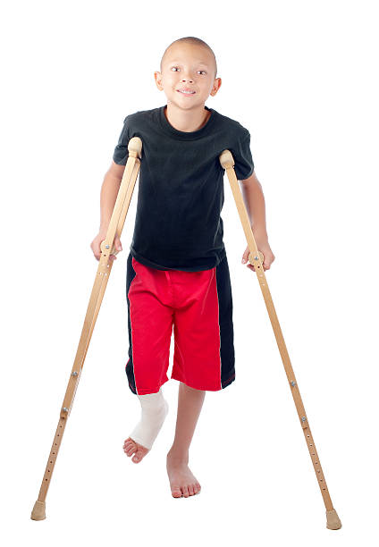Boy with crutches stock photo