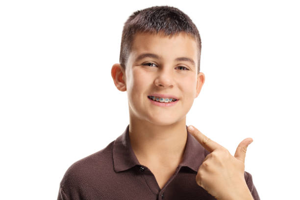 Boy with dental braces pointing on the mouth stock photo
