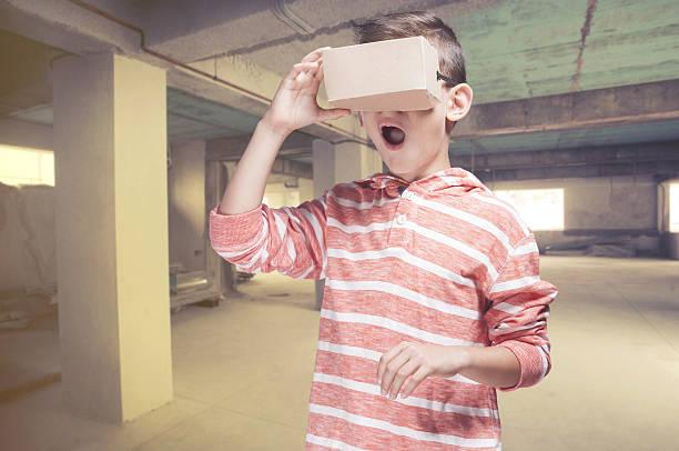 boy with diy virtual reality cardboard headset - roboter bastelarbeiten stock-fotos und bilder