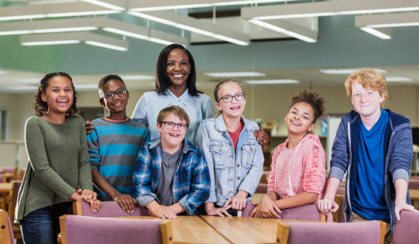 Boy with down syndrome, teacher, classmates in library stock photo