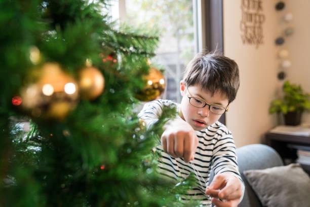 ダウン症候群を持つ少年がクリスマス ツリーを飾る - disabilitycollection ストックフォトと画像