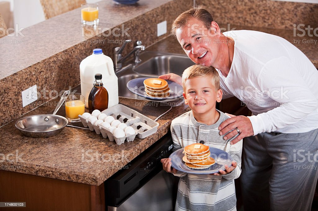 Boy with father having pancakes for breakfast royalty-free stock photo