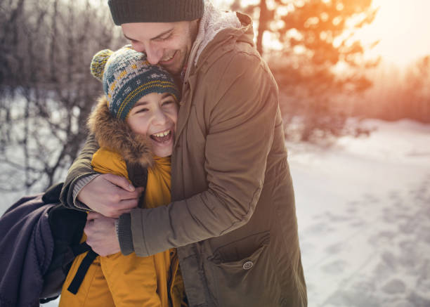Boy with father in winter forest stock photo