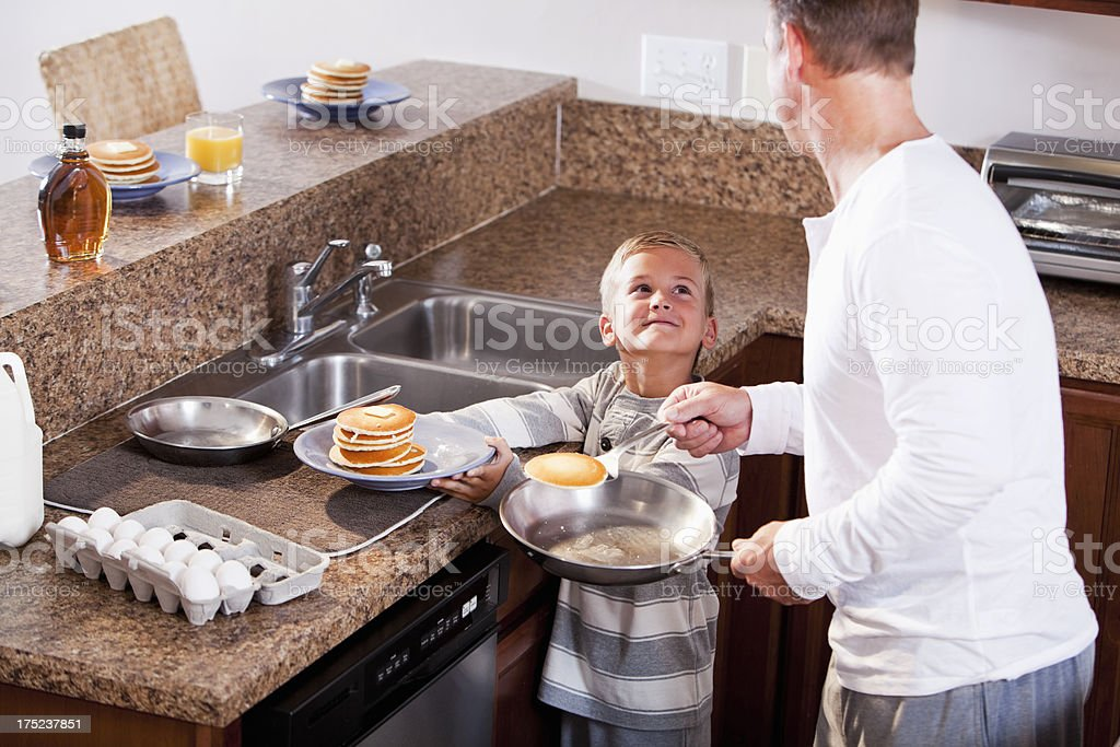 Boy with father making breakfast royalty-free stock photo