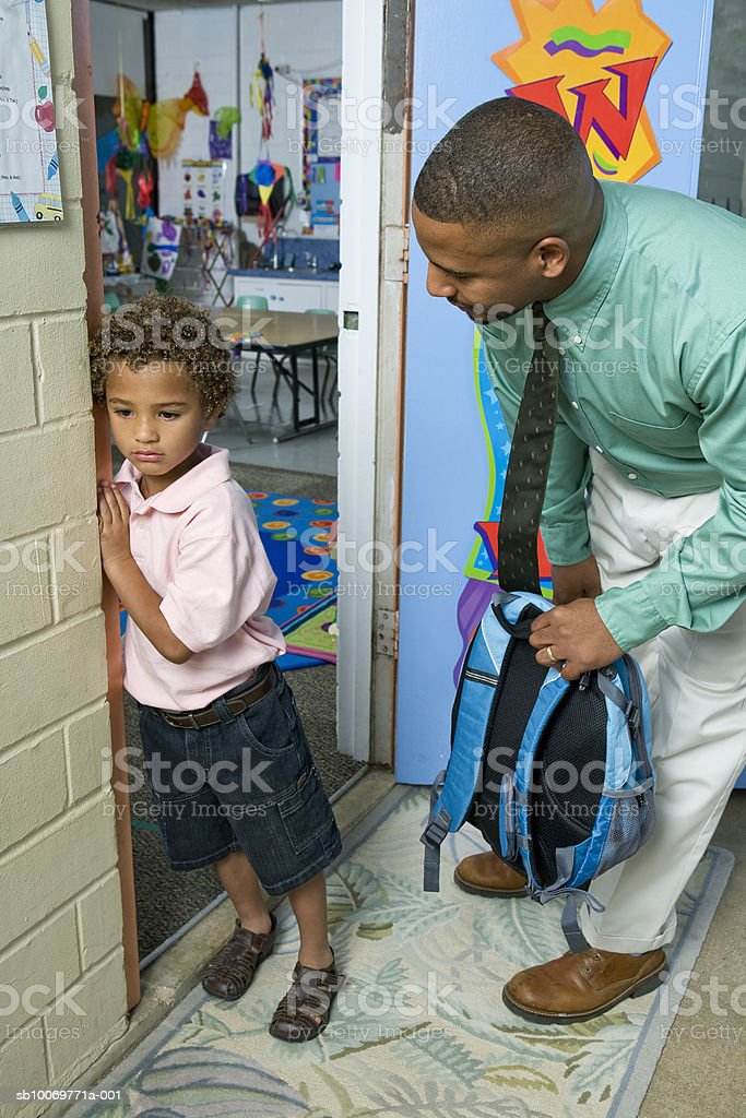 Boy (4-5) with father standing outside classroom foto de stock libre de derechos