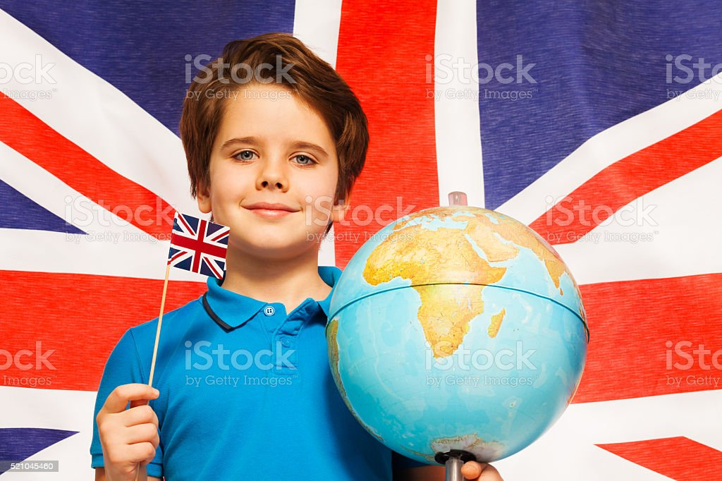 Boy with flag and globe in front of British banner stock photo
