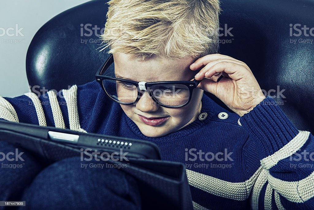 Boy with geek glasses and a digital tablet royalty-free stock photo