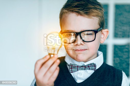 Boy with glasses holds a light bulb in his hand. It lights up: concept of getting a good idea. The boy also wears a bow tie.