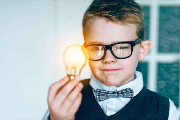 Boy with glasses and bow tie looks at glowing light bulb and gets an idea Boy with glasses holds a light bulb in his hand. It lights up: concept of getting a good idea. The boy also wears a bow tie. child prodigy stock pictures, royalty-free photos & images
