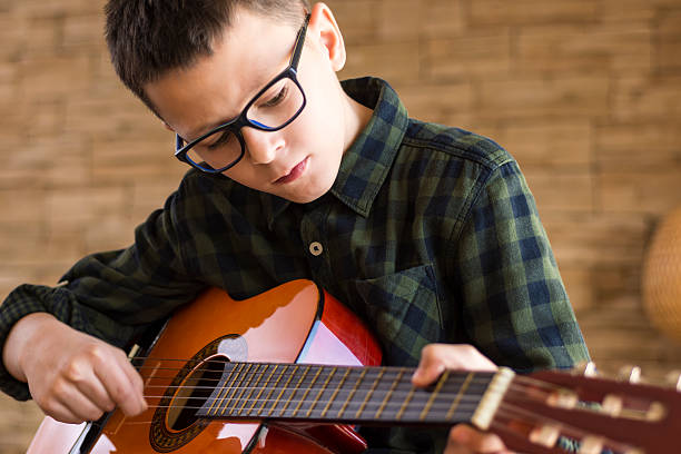 boy with glasses playing acoustic guitar in living room - one song training stock-fotos und bilder