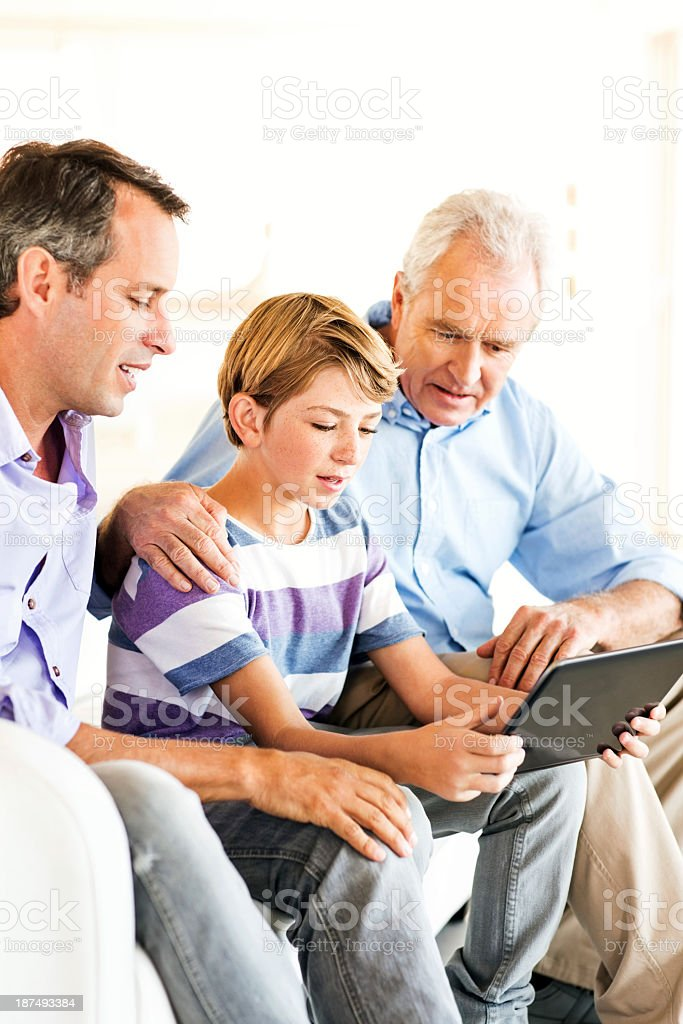 Boy With Grandfather And Father Using Digital Tablet At Home royalty-free stock photo