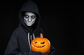 Boy with Halloween makeup holding Jack-O-Lantern  pumpkin looking to side at blank copy space, on black background