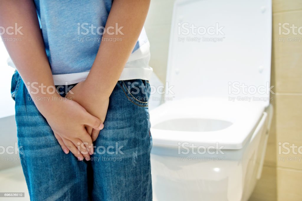 Boy with hands holding his crotch in toilet stock photo