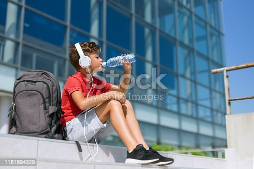 Young boy listening music and drinking water from a bottle