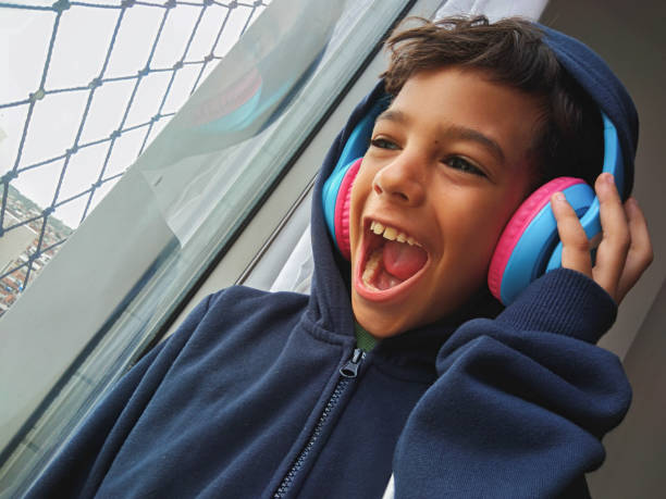 Boy with headphones, looking out the window Boys, Child, Headphones, Listening, Music boy looking out window stock pictures, royalty-free photos & images