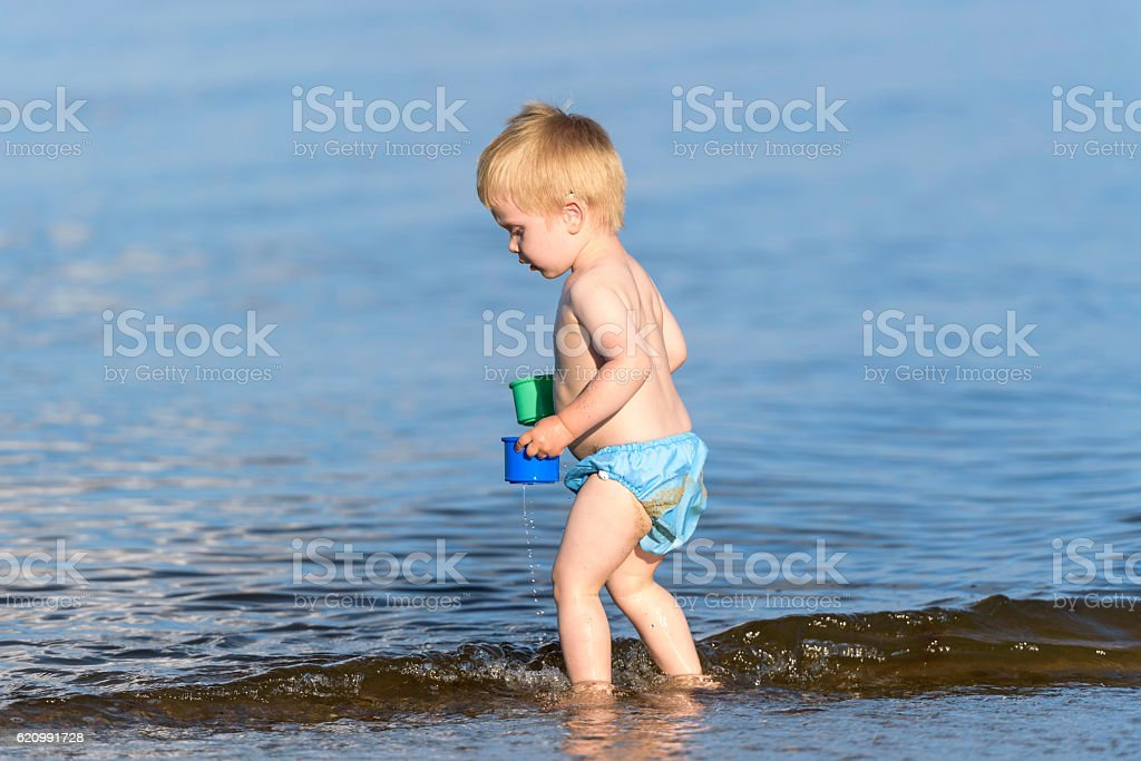 Boy with hearing aid playing in water foto royalty-free