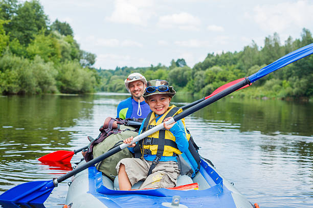 Boy with his father kayaking stock photo
