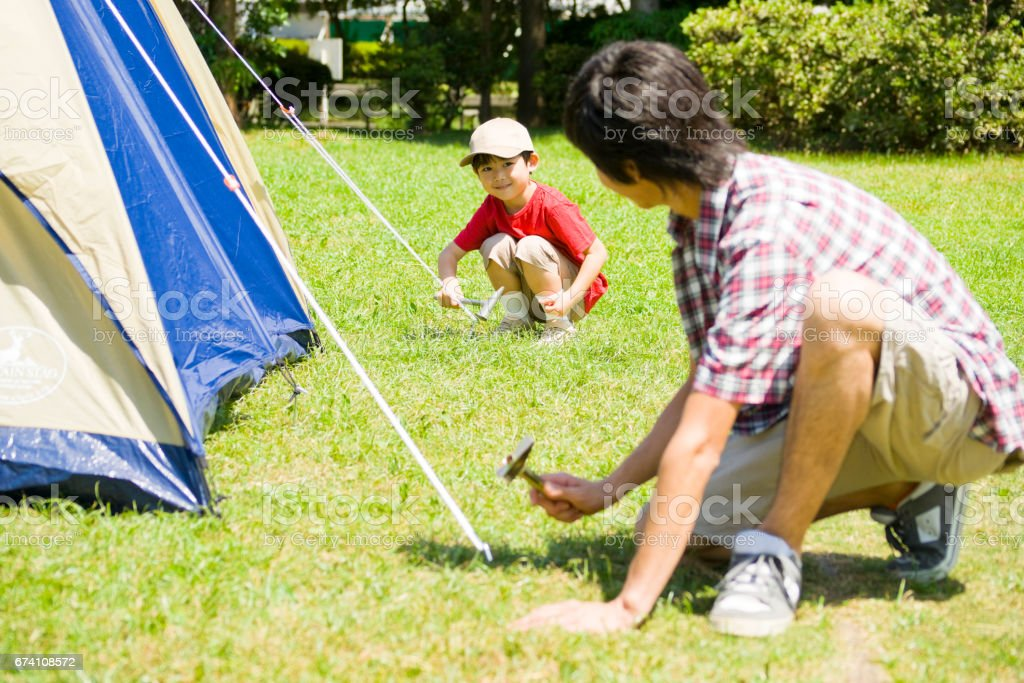 Boy with his father put up a tent royalty-free stock photo