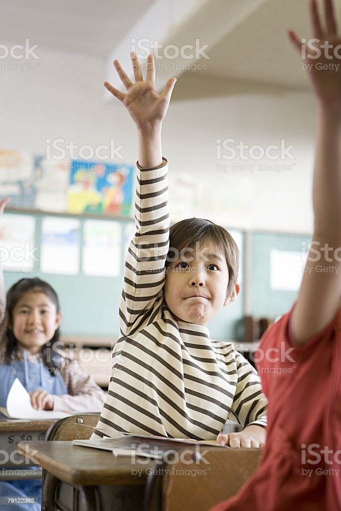 A boy with his hand raised stock photo