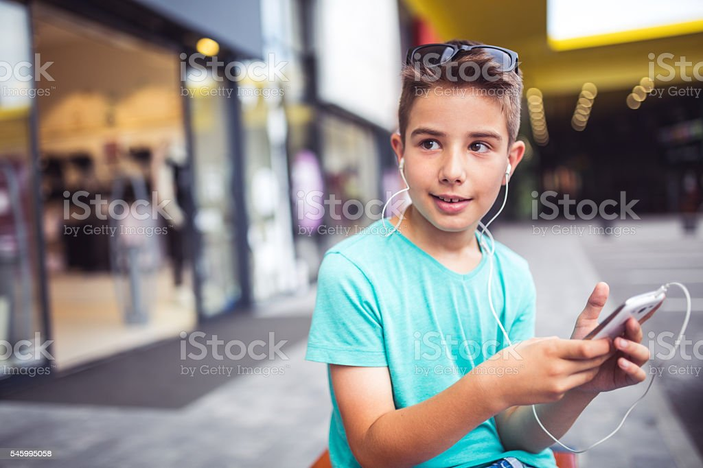 Boy with his mobile phone in a shopping center stock photo