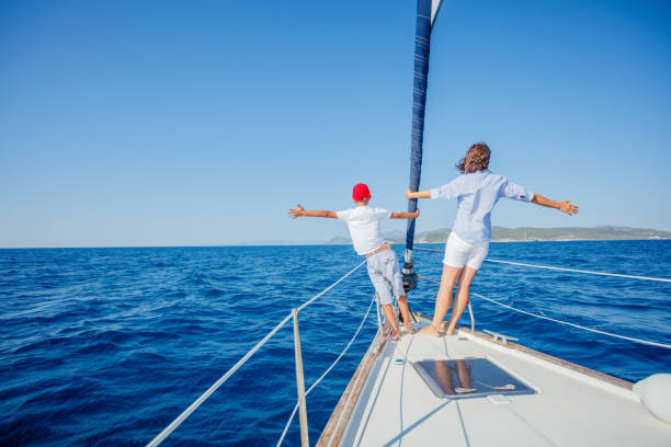 Boy with his mother on board of sailing yacht on summer cruise stock photo
