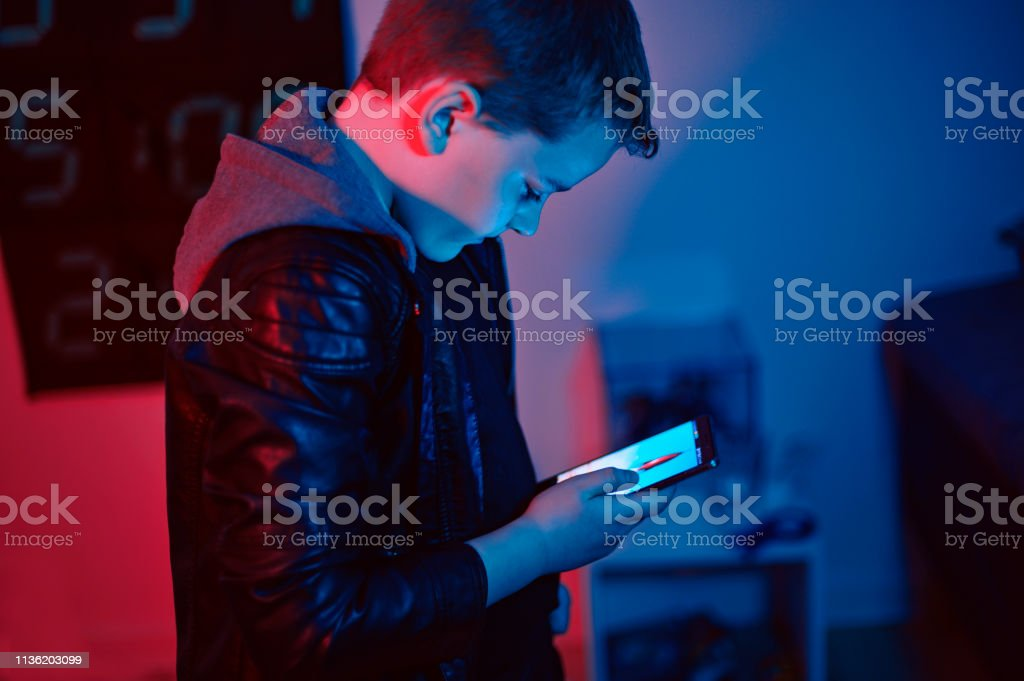 Boy wears leather jacket and a hooded shirt and uses his smart phone...