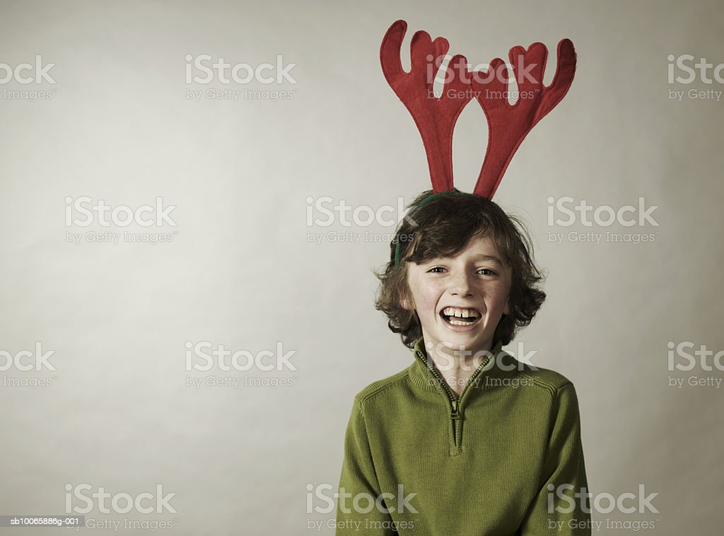 Boy (8-9) with horns, smiling, portrait 免版稅 stock photo