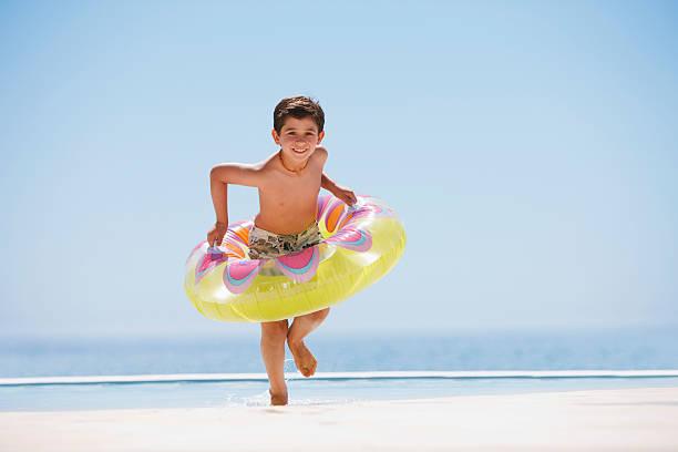 menino com bóia saindo da piscina de borda infinita - com os pés na água - fotografias e filmes do acervo