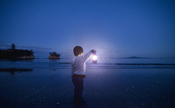 Boy with Lantern in his hand. Boy holding lantern in his hand and looking towards beach. could be waiting for someone or a metaphor of hope or spirituality. lantern stock pictures, royalty-free photos & images