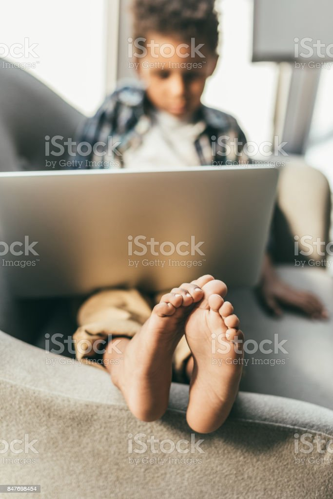 boy with laptop in armchair stock photo