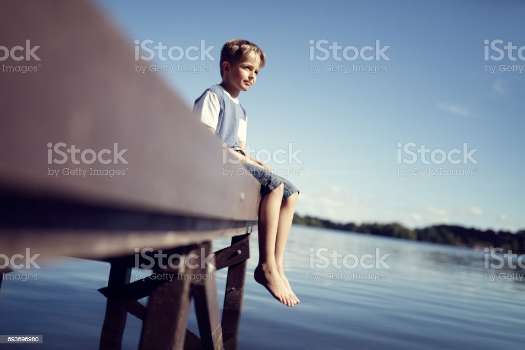Boy with legs dangling from pier stock photo