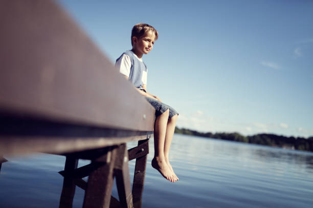 pojke med benen dinglande från piren - flod vatten brygga bildbanksfoton och bilder