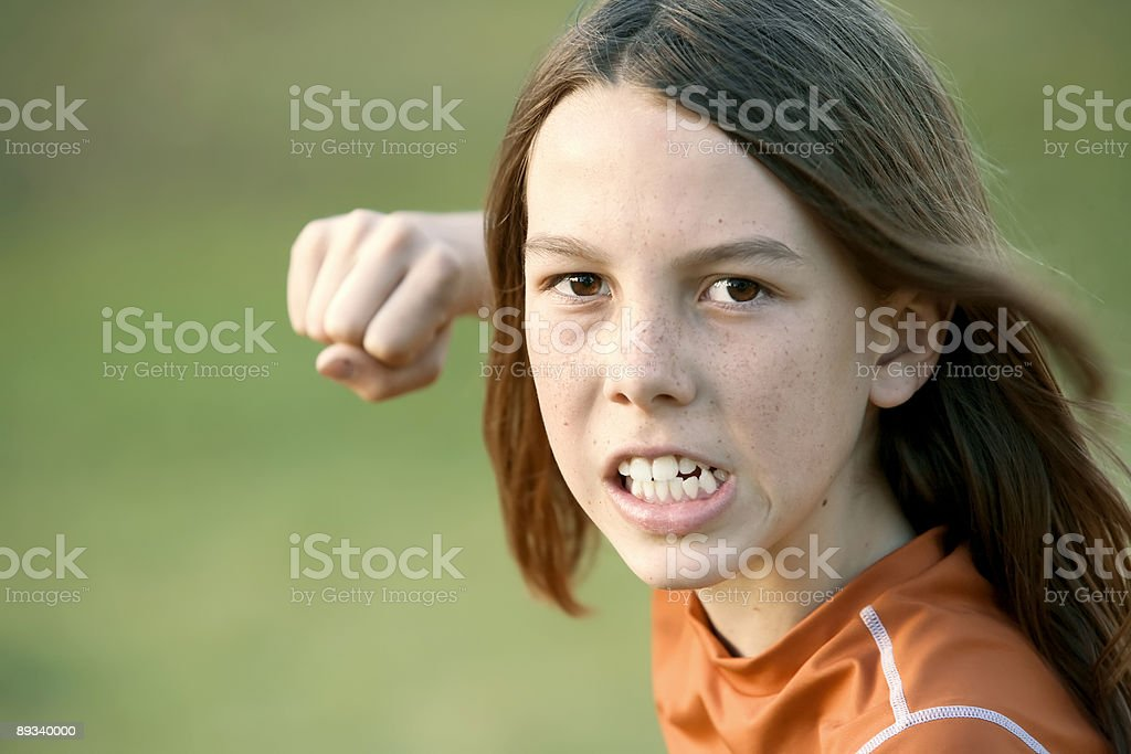 Boy with Long Hair Throws a Punch stock photo