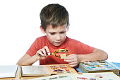 Boy with magnifying glass looks his stamp collection isolated white