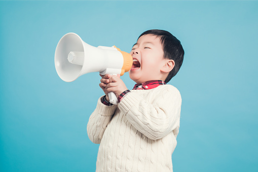 623763462 istock photo Boy with megaphone making an announcement 1135133540