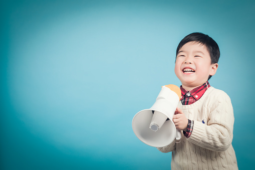 623763462 istock photo Boy with megaphone making an announcement 1135133556